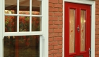 Red composite door in a double glazing showroom in Northampton
